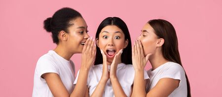 Rumors Concept. Three Young Women Sharing Gossips And Secrets Standing Over Pink Background. Studio Shot, Panorama