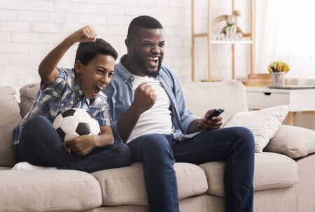 Afro father and son soccer fans watching football on tv at home and emotionaly cheering, sitting with soccer ball on couch in living room