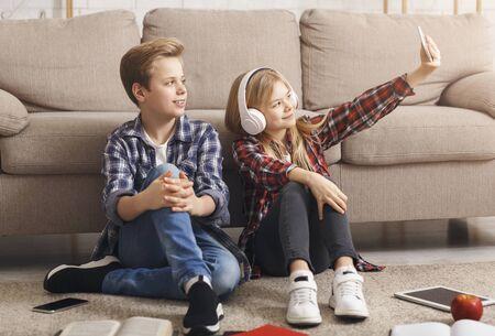 Meilleurs amis. Garçon et fille faisant des selfies sur smartphone s'amusant avec des gadgets assis sur le sol à la maison le week-end.