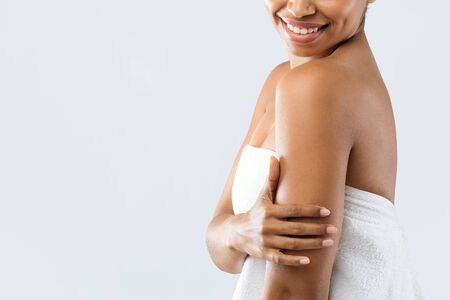 Close up of young beautiful black woman touching her silky arms, copy space, skincare spa procedures