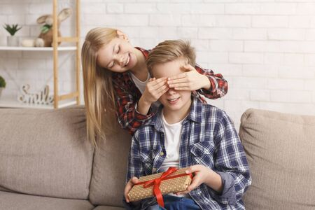 Sister Covering Brothers Eyes Congratulting Him And Giving Birthday Gift Sitting On Sofa At Home. Holidays And Presents Concepts.