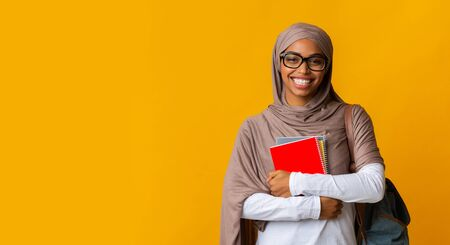 Modern islamic education. Smiling afro muslim female student in headscarf and eyeglasses holding notebooks and looking at camera, yellow background