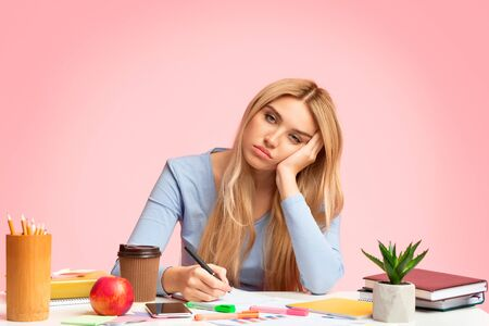 Exhausted Student, Education And Overworking Concept. Tired girl preparing for exams, falling asleep, writing in notebook