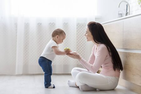 Kind baby. Cute boy giving apple to mom sitting on kitchen floor, free space Stock Photo