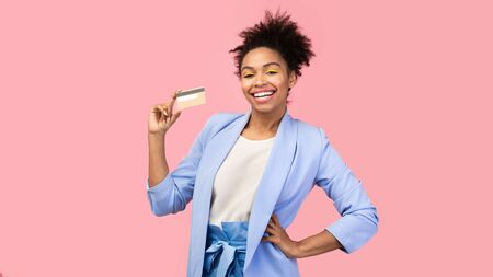 Shopaholic. Happy black woman holding credit card, resting hand on her hip. Copyspace, pink studio wall 版權商用圖片