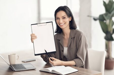 Doing Survey Research. Young woman showing clipboard paperholder working at office, copyspace