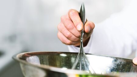 Cooking Food. Unrecognizable Male Chef Using A Whisk Blending Ingredients In Bowl Preparing Dinner In Kitchen Indoor. Panorama, Cropped, Closeup