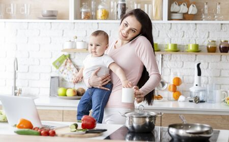 Working at maternity. Young mom talking on phone and holding baby at kitchen, free space