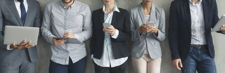 Businesspeople with phones and laptops over grey wall, panorama Stock Photo