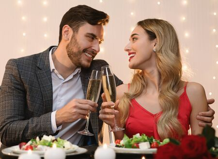 Young Couple Having Romantic Evening In Restaurant, Clinking Glasses With Champagne, Making Toast For Valentines Day Stock Photo