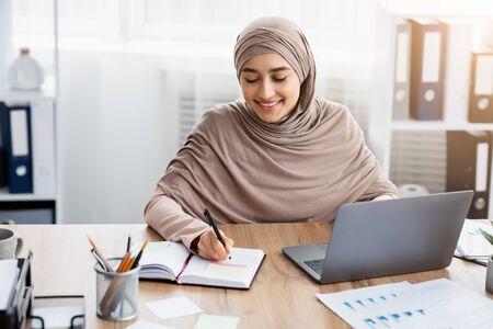 Gestion du temps au travail. Une employée islamique souriante utilisant un ordinateur portable et écrivant des notes, gérant son emploi du temps au bureau