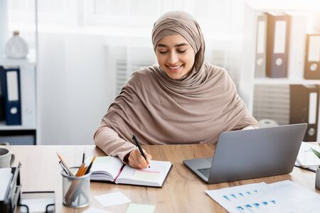 Time Management At Work. Smiling Islamic Female Employee Using Laptop And Writing Notes, Managing Her Business Schedule In Office