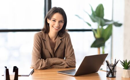 Successful Businesswoman. Portrait of confident female manager sitting at desk, looking at camera, copyspace