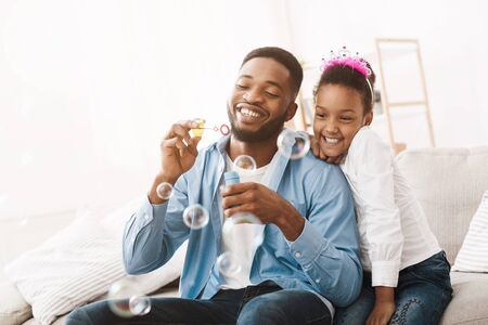 Fatherhood concept. Daddy and daughter blowing soap bubbles, playing together at home Stock fotó