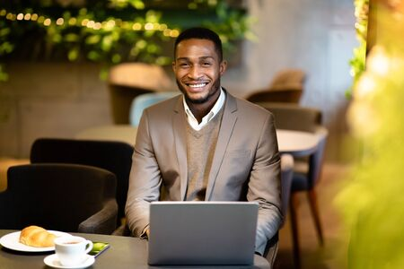 Male Executive. Smiling afro businessman working in modern cafe, looking at camera, using computer, free space