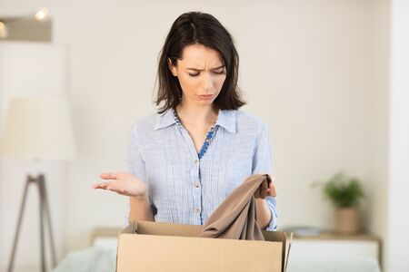 Puzzled Young Woman Taking Clothes Out Of Box, Holding Shirt, Getting Home Delivery By Mistake, Copyspace