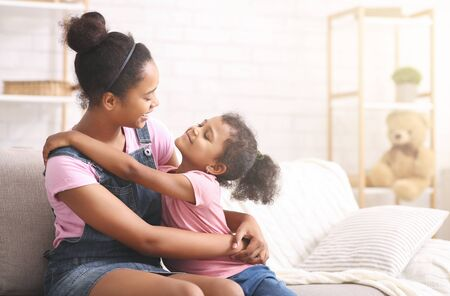 Familie liefde. Vrolijke Afrikaanse zussen knuffelen thuis, lege ruimte Stockfoto