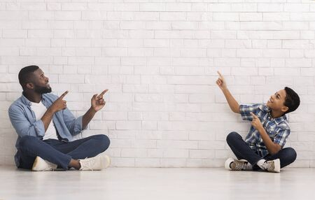 Free Space For Your Ad. Happy Black Father And Little Son Sitting On Floor Near White Brick Wall And Pointing At Empty Space Imagens