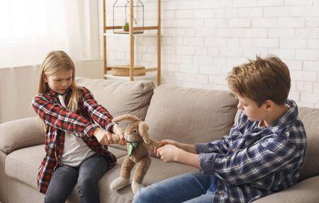 Chciwy Brat I Siostra Dzieci Wyciągając Zabawkę Nie Chcąc Dzielić Siedząc Na Sofie Wewnątrz. Zły związek rodzeństwa
