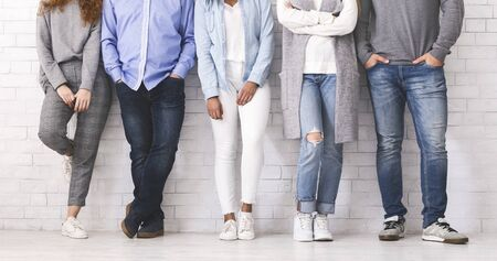 Alcoholics Anonymous Concept. Legs of unrecognizable diverse people standing in row against white brick wall, panorama Stock Photo