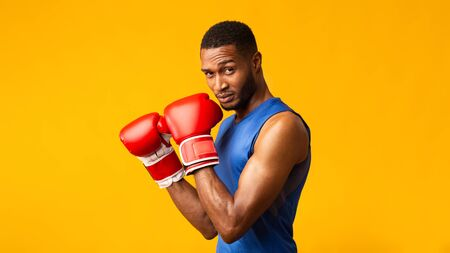 Boxing Stance. Muscular black guy in red gloves looking at camera isolated over yellow studio wall, copyspace