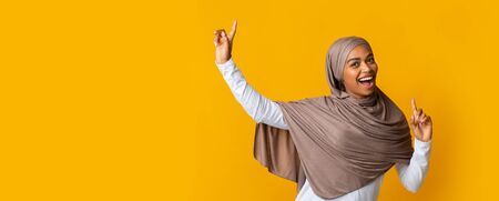 Entertainment For Muslim Women Concept. Cheerful Black Islamic Girl In Hijab Having Fun, Dancing And Singing With Raised Hands Over Yellow Background