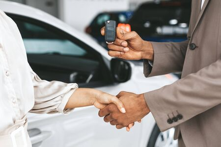 Car Sales. Unrecognizable Seller Greeting Lady Buyer With Handshake And Giving Key Standing Near Automobile In Dealership Store. Cropped Stockfoto