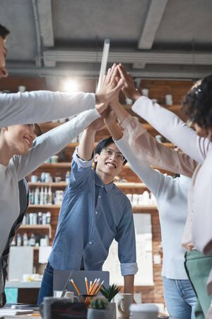 Team inspiration concept. Young asian manager giving high five to his international team, having business meeting in office Stock Photo