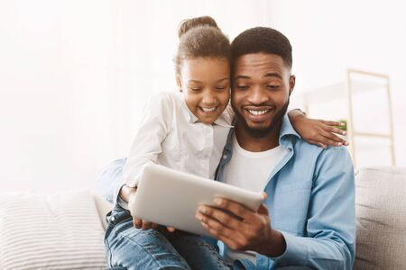 Family time. Young father teaching daughter to use digital tablet, free space