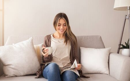 Home and leisure concept. Smiling woman sitting on couch and reading magazine with coffee at home