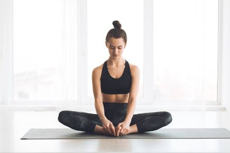 Pilates. Calm girl working out doing yoga exercise, sitting in baddha konasana, bound angle or butterfly pose, copyspace
