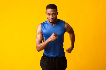 Move On. Confident afro sportsman getting ready for run, looking at camera isolated over yellow studio wall, copyspace 스톡 콘텐츠