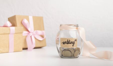 Cash money coins in glass jar with text written for wedding over gray background, panorama, concept of saving or planning budget for wedding day