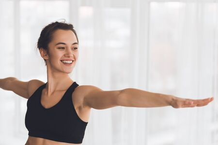 Smiling woman doing yoga exercise practicing warrior pose in modern studio, standing next to window, copyspace Stock Photo