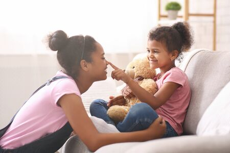 Playtime. Cute african american sisters playing together at home