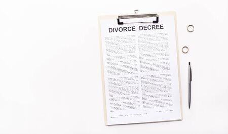Divorce decree law document, wedding rings and pen on white background, copy space, panorama