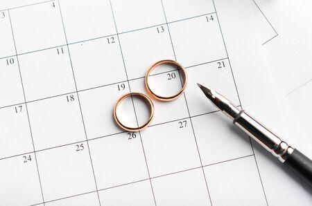 Golden Wedding Rings on Calendar symbolizing wedding date or anniversary, choosing date concept Reklamní fotografie