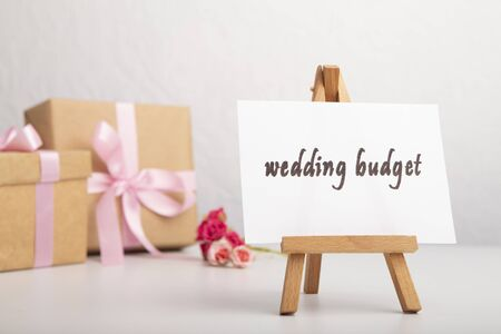 Wedding word on easel, present boxes on a table. Saving money for wedding concept. Planning for future expenses and to make targeted savings. Фото со стока