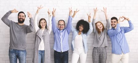 Positive Work Environment. Portrait Of Diverse Happy People Showing Funny Gestures While Posing Together Over White Brick Wall Background, Panorama