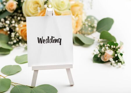 Wedding composition. Small easel with text on creative background with roses
