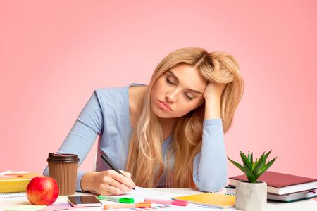 Sleep At Work. Portrait of sad blonde student sitting at table resting head on hand and writing, copyspace Imagens