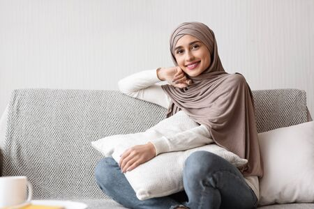 Pretty Muslim Housewife Smiling At Camera On Sofa At Home, Holding Pillow While Sitting On Comfortable Couch In Living Room, Copy Space