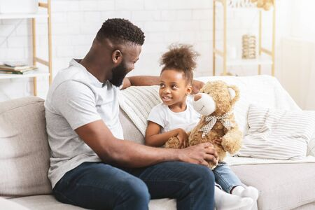Little african girl playing with her handsome cheerful dad at home, free space Archivio Fotografico - 140883659