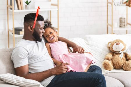 Cute little black girl wearing crowns with her young daddy, sitting on couch at home and bonding, copy space 版權商用圖片