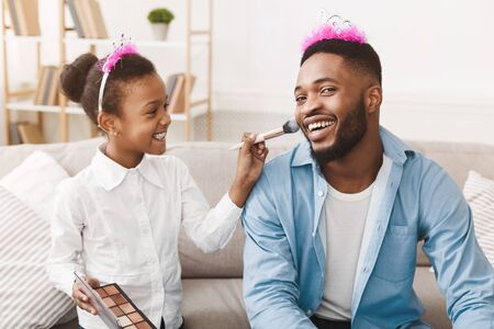 Play together. Little princess putting makeup on her queen father, spending time at home