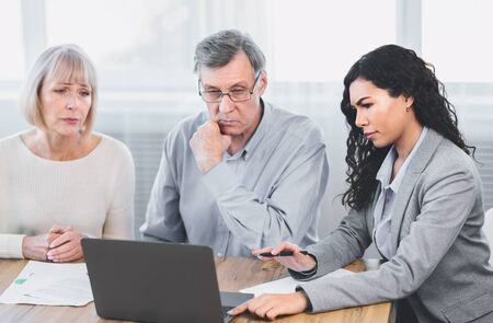 Insurance Concept. Sad senior couple consulting with female agent at office, using laptop computer Standard-Bild