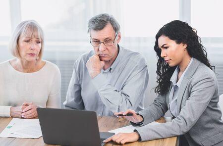 Concepto de seguro. Triste pareja senior consultando con agente femenino en la oficina, utilizando equipo portátil Foto de archivo