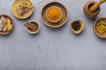 Ingredients for turmeric latte. Ground turmeric, curcuma root, cinnamon, ginger, honeycombs in wooden bowls on gray background. Top view, copy space