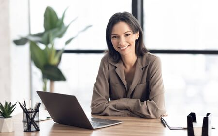 Small Business Entrepreneur. Portrait of smiling european girl sitting at desk, looking at camera, copyspace