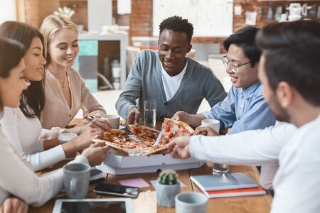 Hungry young international team of employers grabbing slices from delivery pizza, office lunch break